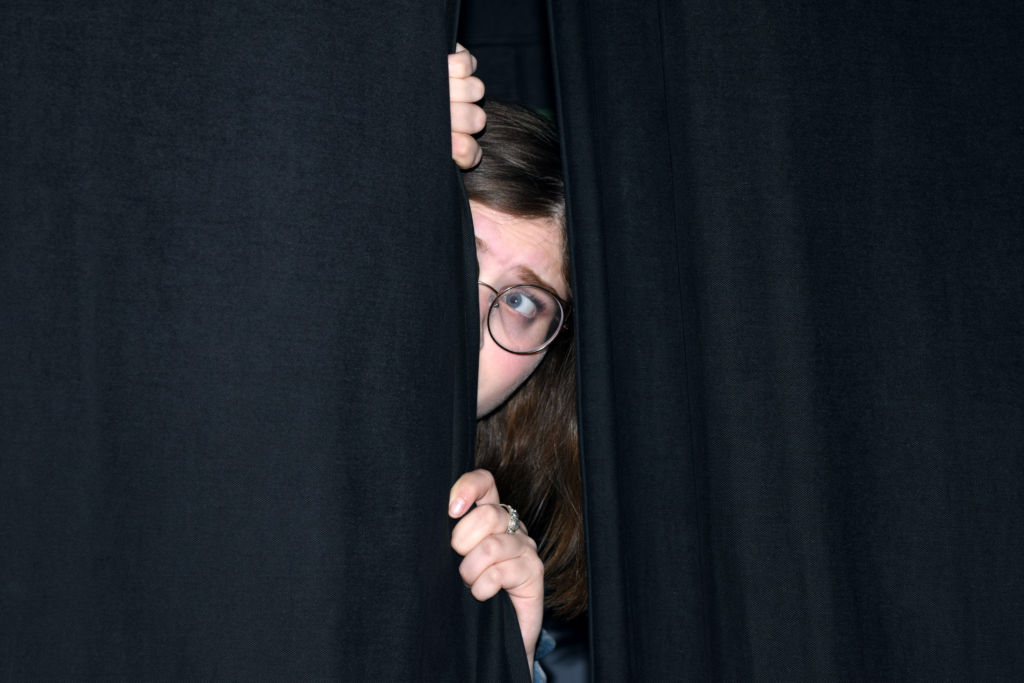 Photo of someone hiding behind show curtain